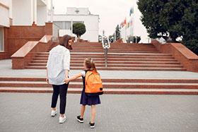 Imagen ilustrativa de una madre acompañando a su hija a la escuela.